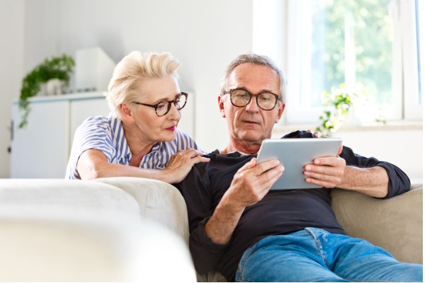 Senior couple using a digital tablet together at home