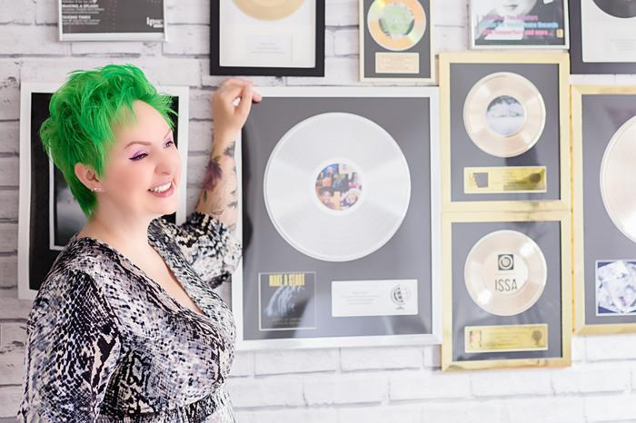 Rachel Mason standing in front of a wall of  framed records
