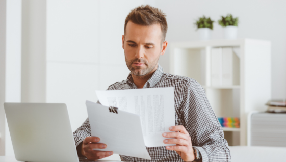 Self-employed man working at home looking at a work contract