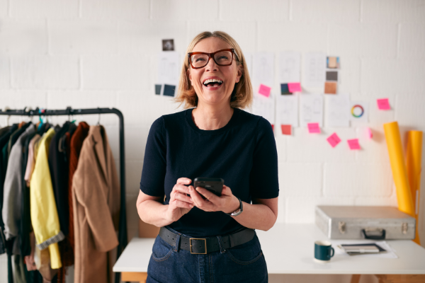 A self-employed woman smiling at her phone
