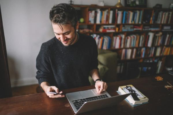 freelancer using his phone for social media at desk in home office